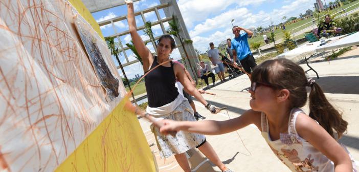 Artista e criança pintam a tela no café da Biblioteca Parque Villa-Lobos.