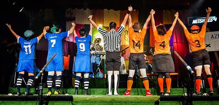 Sete palhaços da Cia. do Quintal, estão de costas, com os braços levantados, saudando a platéia do teatro onde se encontram.