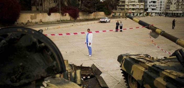 Um homem, provavelmente um médico ou profissional da saúde. devido às roupas, está no meio de dois tanques de guerra.