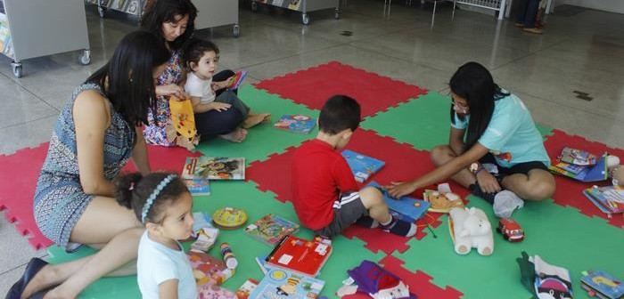 Crianças e adultos brincam e leem livros educativos.